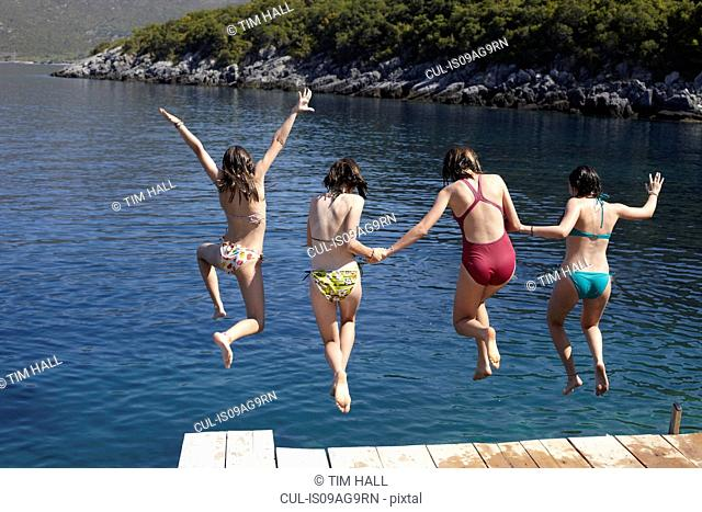 Four girls jumping from pier into the sea