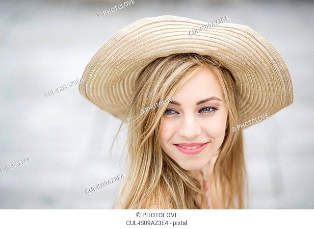 Portrait of beautiful long haired young woman wearing straw hat in city