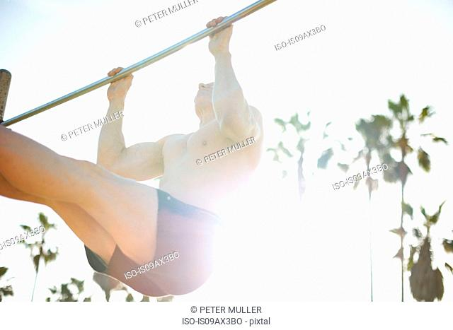 Low angle view of man, legs raised doing pull up on gymnastic bar