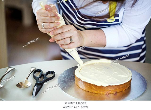 Close up of person wearing a blue and white stripy apron, holding a piping bag, decorating a cake with cream, spoons and scissors on table