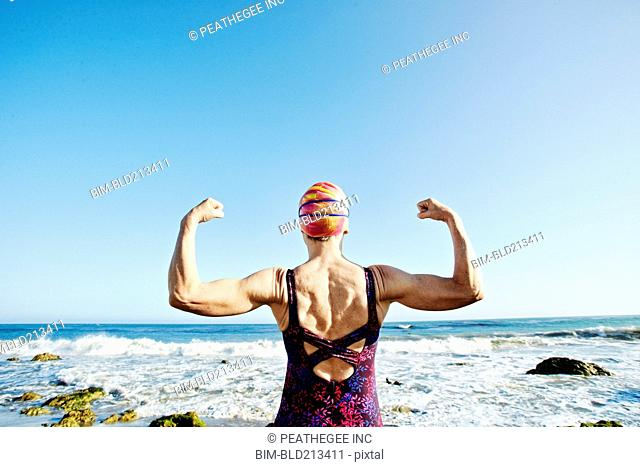 Older Caucasian woman flexing her muscles on beach