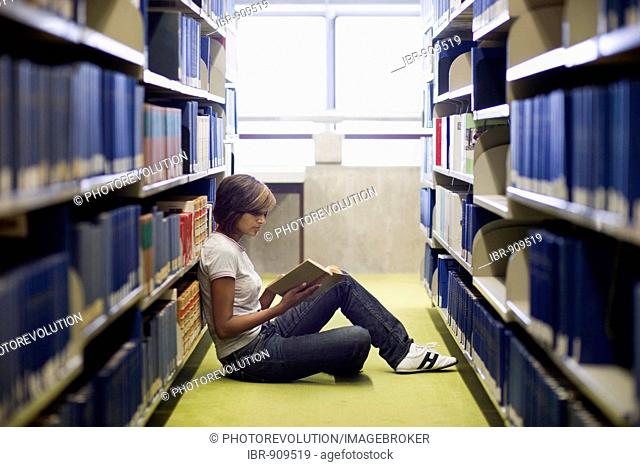 Young dark-haired female student reading a book while sitting between the bookshelves in a library