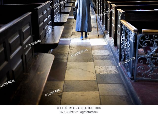 Unrecognizable old lady walking for the corridor of a church. London, England