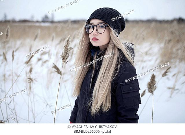 Serious Asian girl standing in field in winter