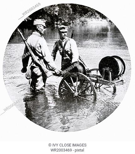 In this photo, Austrian soldiers are shown laying a field telephone line across a stream during World War I—in late 1914, early 1915