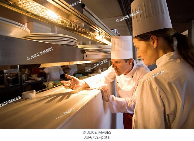 Male and female chefs standing at order counter in commercial kitchen, agitated male chef gesturing to restaurant staff
