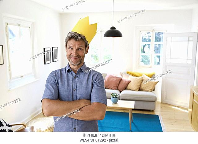 Mature man at home wearing paper crown, looking content