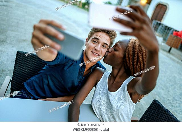 Young couple taking selfies at outdoor cafe