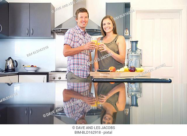 Caucasian couple drinking juice in kitchen