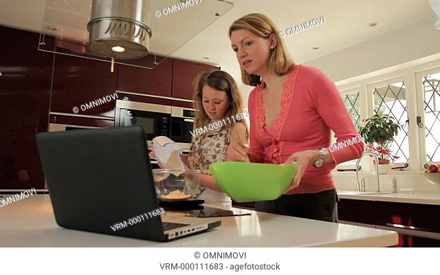 Mother and Daughter Cooking in Kitchen, Laptop on Counter