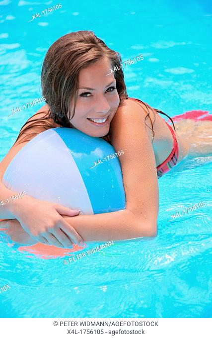 Young woman with a water ball in Pool