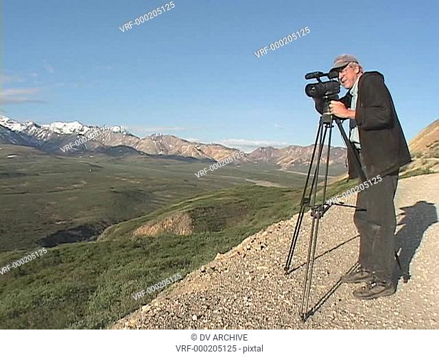 A filmmaker records a nature scene in a grassy, mountainous area