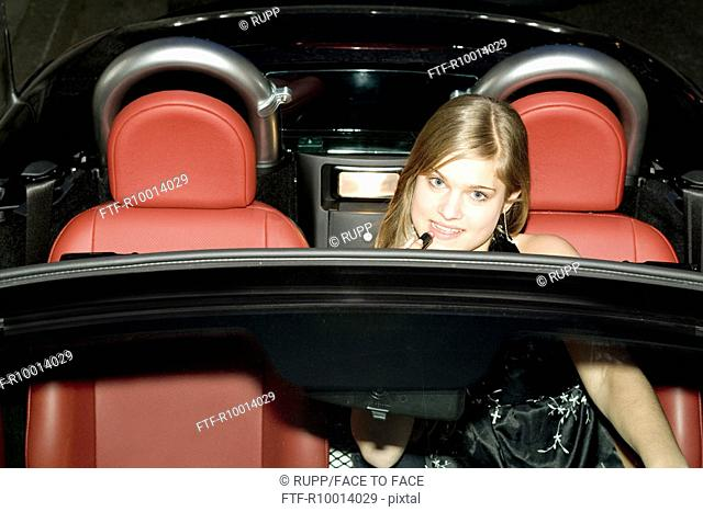 Blond woman making oneself up in a mirror of the car