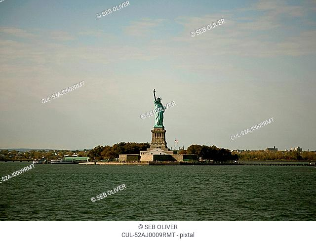 Statue of Liberty on island in harbor