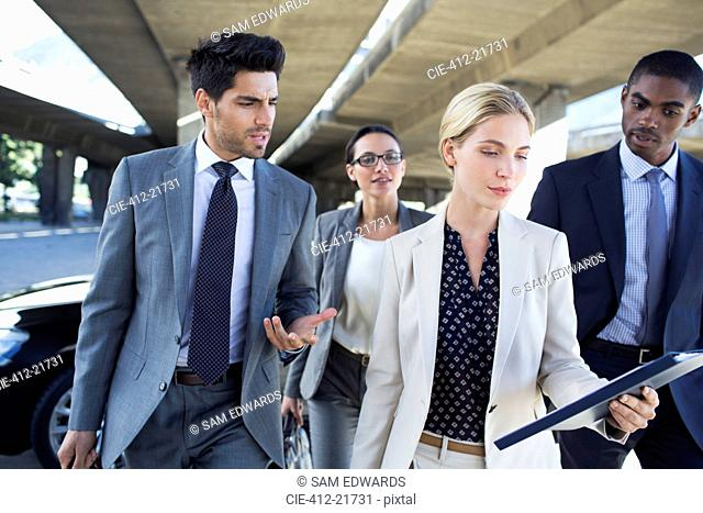 Business people walking under city overpass