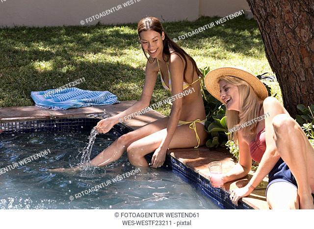Two young women having fun at swimming pool
