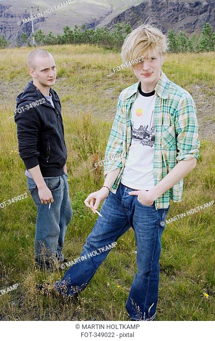 Two young men smoking in field