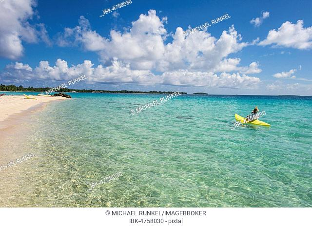 Female tourist kayaking in the turquoise waters of Tikehau, Tuamotu Archipelago, French Polynesia