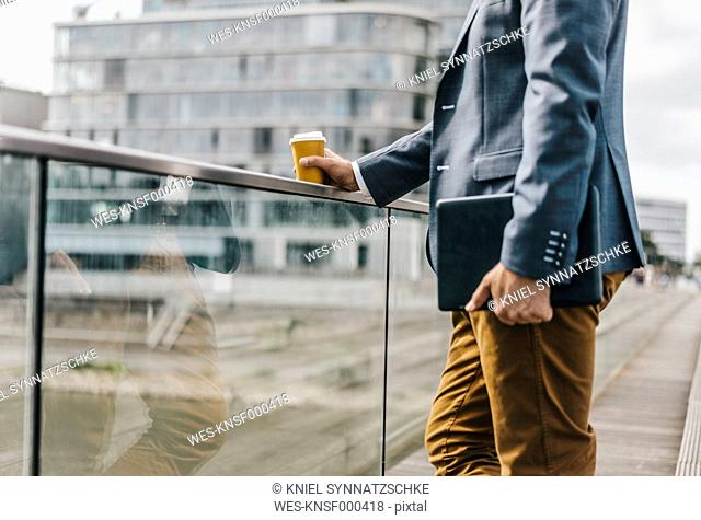 Businessman standing on bridge with coffee and tablet
