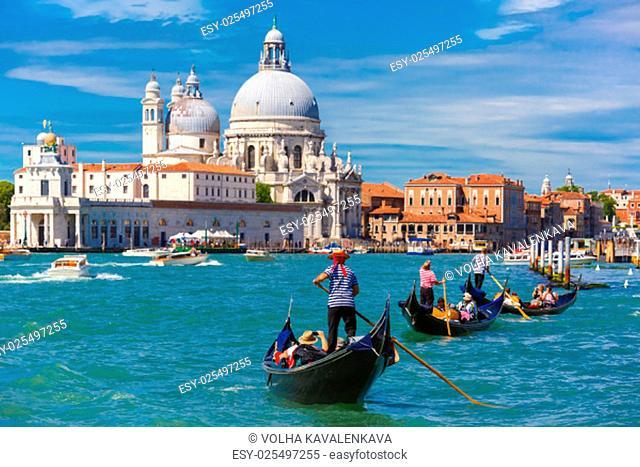 Picturesque view of Gondolas on Canal Grande with Basilica di Santa Maria della Salute in the background, Venice, Italy. Selective focus on Gondolier