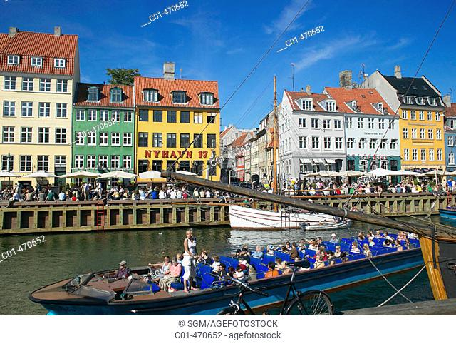 Tour boats, moored sailboat, ancient houses and waterfront cafe terraces at Nyhavn ('New Harbor'), Copenhagen. Denmark