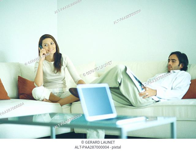 Man and woman sitting on couch, man reading while woman uses cell phone