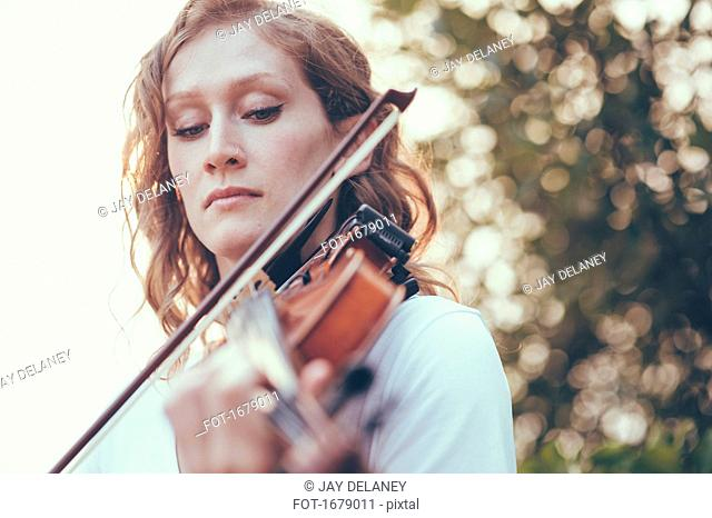 Close-up of young woman playing violin