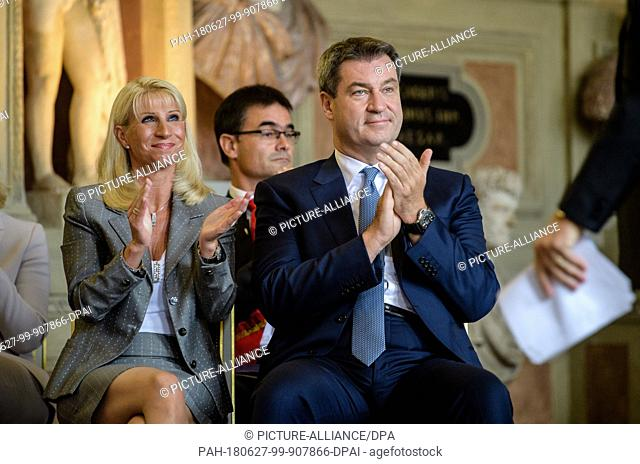 27 June 2018, Germany, Munich: Premier of Bavaria, Markus Soeder of the Christian Social Union (CSU), and his wife Karin applaud during the presentation of the...