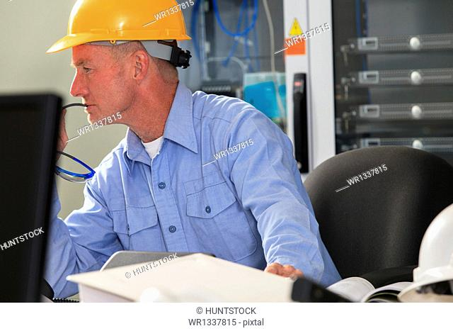 Electrical engineer studying monitor for performance in operations room of electric power plant