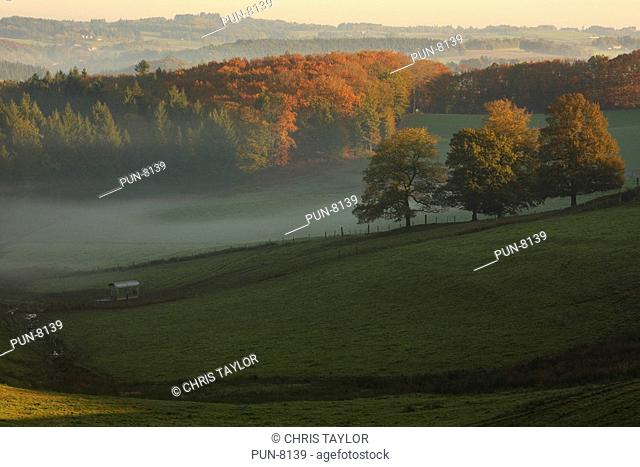 View across a misty valley at sunrise in the Limousin region of France