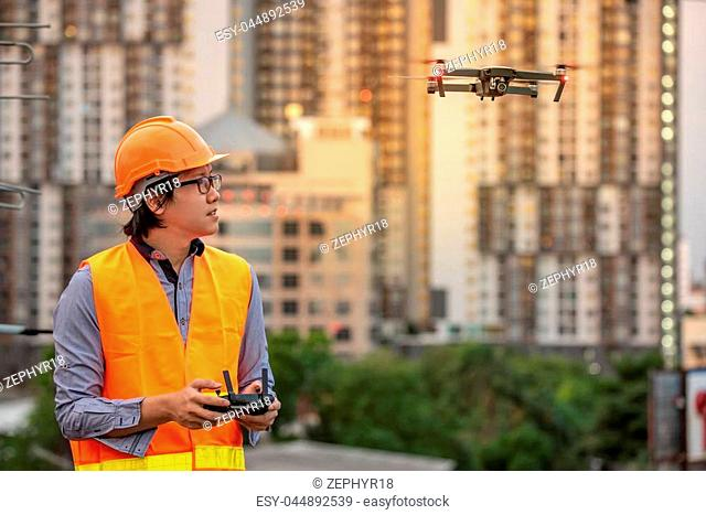 Young Asian engineer flying drone over construction site. Using unmanned aerial vehicle (UAV) for land and building site survey in civil engineering project