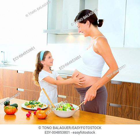 Beautiful pregnant mother with her daughter at kitchen preparing salad