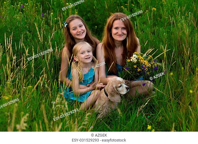 mother and two smiling daughters sitting on the grass at the evening field
