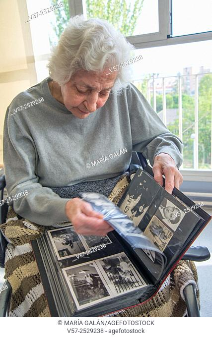 Old woman leafing through a family photo album in a nursing home