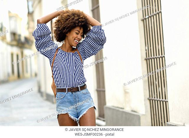 Portrait of fashionable young woman with curly brown hair on the street