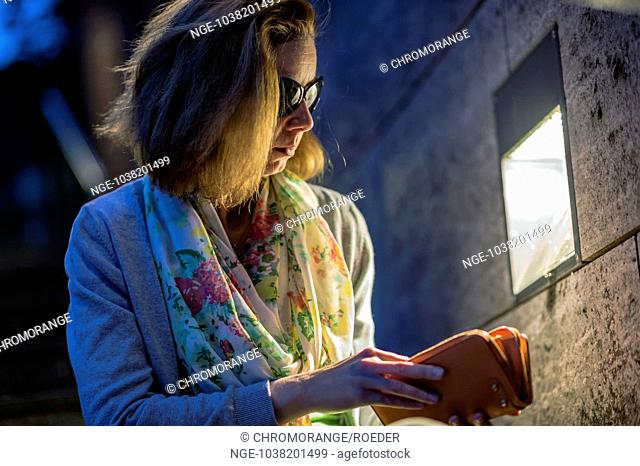 young woman sitting on a staircase and seeking money in her purse