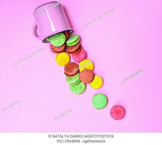 Colorful pastry made of egg whites and almond flour on a pink background, French cookies macaron