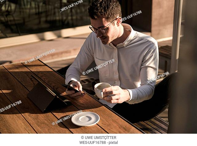 Young man using cell phone and tablet at outdoor cafe
