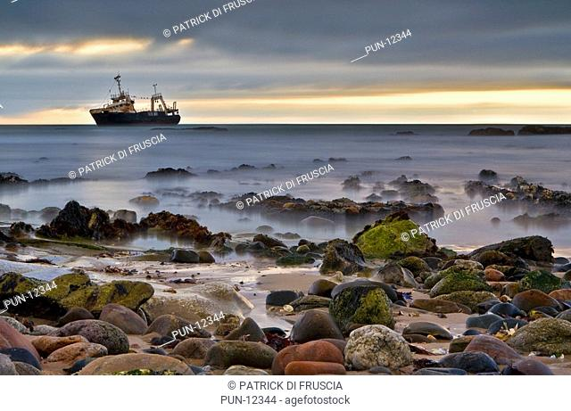 An old abandoned shipwreck ghost type ship at dusk located and complimented by colourful rocks along the coast