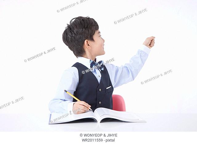 a boy studying with an open book in front of him