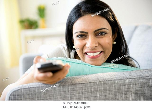 Indian woman watching television on sofa
