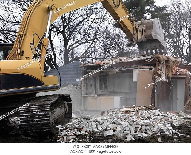 Excavator demolishing a house. Toronto, Canada