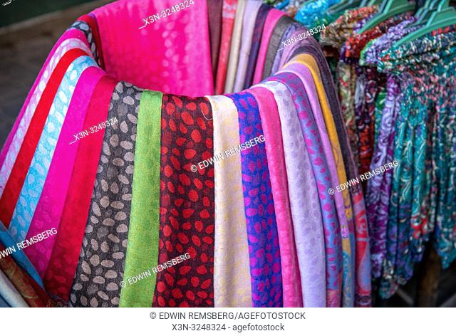 Variety of colorful scarves displayed neatly for sale at outdoor marketplace, Marrekech, Morocco