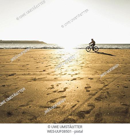 France, Crozon peninsula, Man biking on the beach