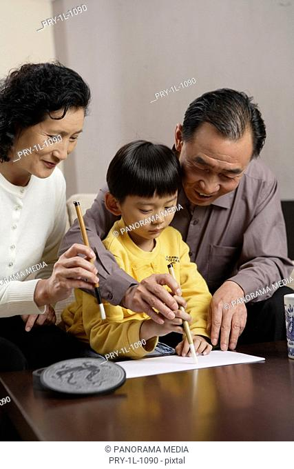 Grandfather and Grandmother practising Chinese calligraphy with grandson