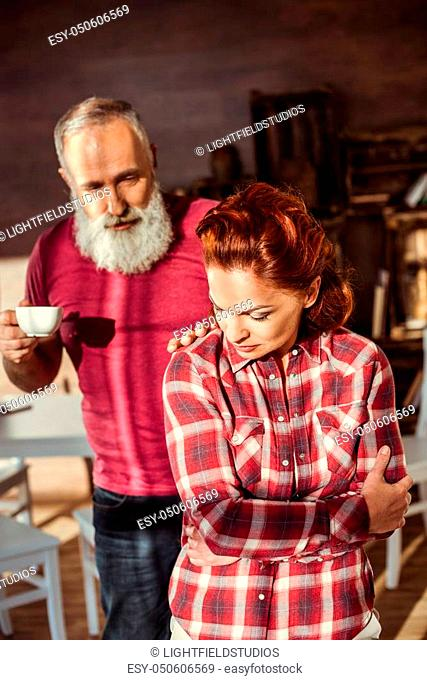 Mature bearded man with coffee cup talking to dissatisfied woman