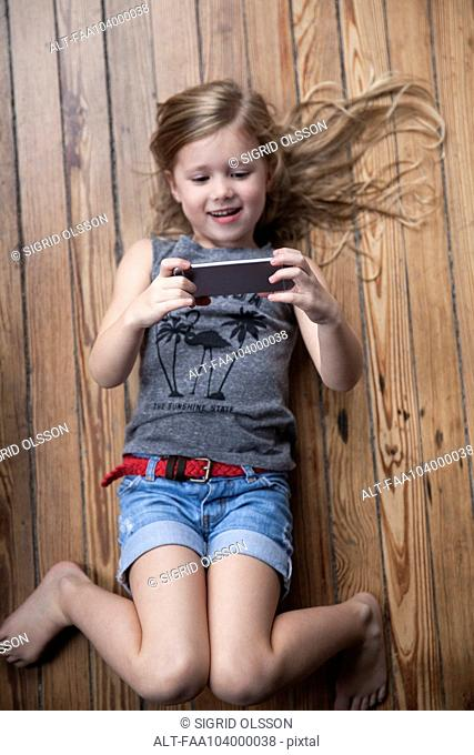 Little girl lying on floor using smartphone