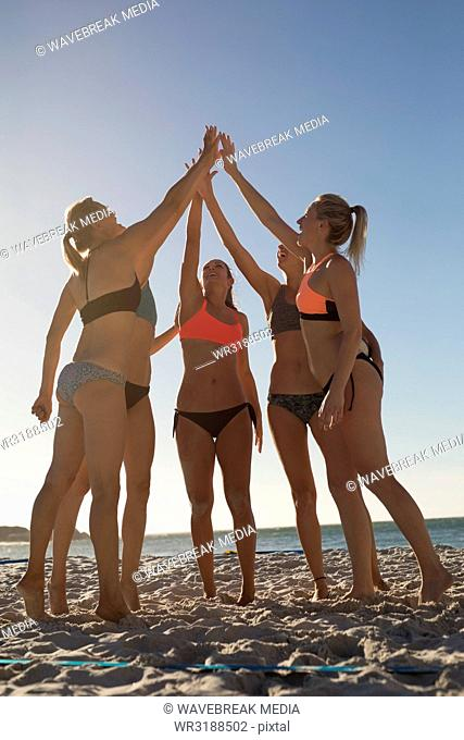 Female volleyball players giving high five to each other