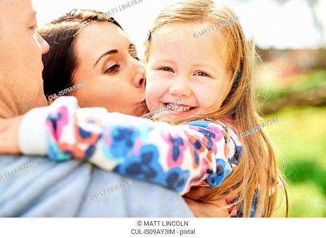 Over shoulder view of mother kissing smiling daughter on cheek