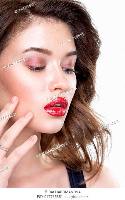 Fashion Makeup Model with perfect makeup, red lips and smooth, clean skin. Highlighter